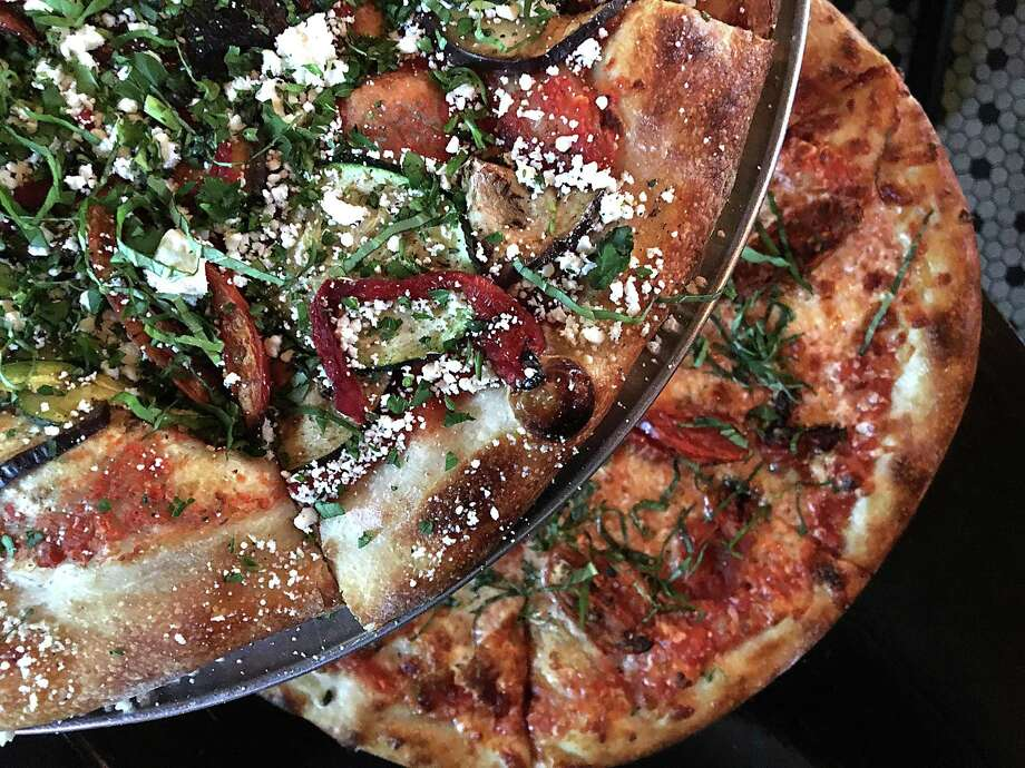 Summer vegetable pizza with eggplant, zucchini, red bell peppers and herbs (top) and a custom-order pizza with basil, roasted tomatoes and smoked mozzarella cheese from Barbaro. Photo: Mike Sutter /San Antonio Express-News