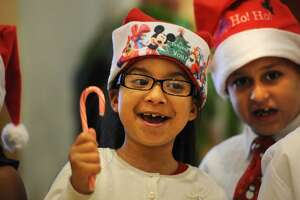 Wilbur Cross School second graders Kayla Dipres, left, Eliezer Ortiz, and their classmates recite Christmas poems during the 12th Annual Christmas Tree Lighting ceremony at St. Vincent's Medical Center in Bridgeport, Conn. on Monday, December 1, 2014.