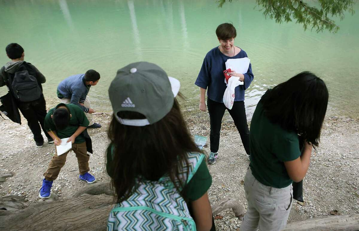 Joey Fauerso, a Texas State University art professor who has been commissioned to paint a mural, shows a group of fourth-graders from Cotton Academy the river during a nature appreciation field trip to Guadalupe River State Park, on Nov. 2, 2017. Fauerso was gathering ideas and words from the students for the mural.