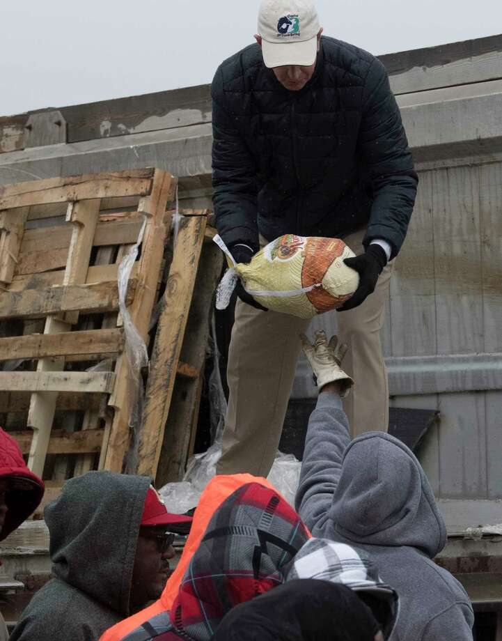 Shannon Donovan hands down one of the 1000 turkeys to James Jackson both of OTB that have been donated by local businessman and horseman Roddy Valente to be handed out at the Albany OTB to those in need for Thanksgiving Wednesday,  Nov. 22, 2017 in Albany, N.Y.    (Skip Dickstein/ Times Union) Photo: SKIP DICKSTEIN, Albany Times Union