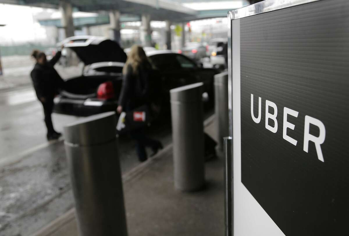 FILE - In this March 15, 2017, file photo, a sign marks a pick-up point for the Uber car service at LaGuardia Airport in New York. Uber is coming clean about its cover-up of a year-old hacking attack that stole personal information about more than 57 million of the beleaguered ride-hailing service's customers and drivers. The revelation Tuesday marks the latest stain on Uber's reputation. (AP Photo/Seth Wenig, File)