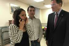 Fanny Torres clutches a phone next to her husband, Marco Reyes Alvarez, after learning Reyes received a temporary reprieve on Wednesday at First and Summerfield United Methodist Church in New Haven. On far right, U.S. Sen. Richard Blumenthal looks on while the couple receives the news at the church were Alvarez, an undocumented resident, had been living.