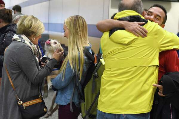Brenda McGuire of Shushan, N.Y., left, and her husband John McGuire, second from right, greet their daughter Maddie Martelli, holding her dog Dez, and husband Matt Martelli from Seattle home for the holiday at the Albany International Airport on Wednesday, Nov. 22, 2017 in Colonie, N.Y. (Lori Van Buren / Times Union)