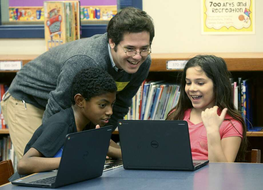 Fourth graders Atom Bobadilla, left, and Karina Gallegos, both 9, take part in the Literacy San Antonio/SAReads program at Southwest Elementary School Nov. 8. The necessity of such programs is evident in the city's ranking in literacy, which involves more than the ability to read. Photo: John Davenport /San Antonio Express-News / ©John Davenport/San Antonio Express-News