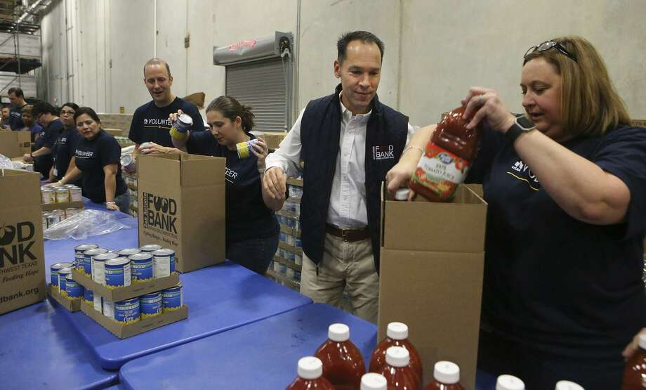 Eric S. Cooper, (second from right) CEO of the San Antonio Food Bank, packs boxes of food for seniors with volunteers from USAA at the San Antonio Food Bank. According to Cooper, the Food Bank serves 16 counties in the San Antonio area. The San Antonio Food Bank is on a 40-acre campus and has about 200 employees. Photo: John Davenport /San Antonio Express-News / ©John Davenport/San Antonio Express-News