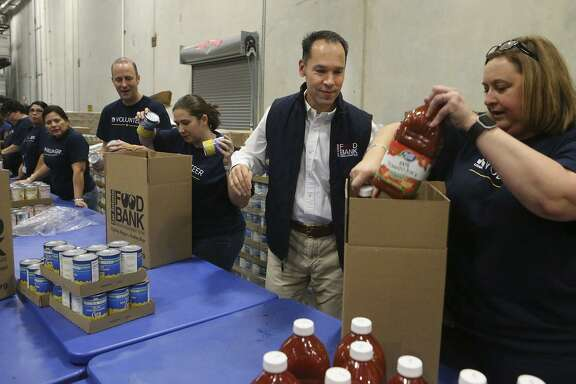Eric S. Cooper, (second from right) CEO of the San Antonio Food Bank, packs boxes of food for seniors with volunteers from USAA at the San Antonio Food Bank. According to Cooper, the Food Bank serves 16 counties in the San Antonio area. The San Antonio Food Bank is on a 40-acre campus and has about 200 employees.