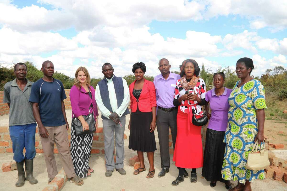Tina Kahlig, vice president of the Children In Need board, poses for a photo with parents and teachers at a school in Mazabuka, Zambia. Children In Need was founded 15 years ago in an effort to help children and families living in extreme poverty in Zambia, a landlocked country in Southern Africa.