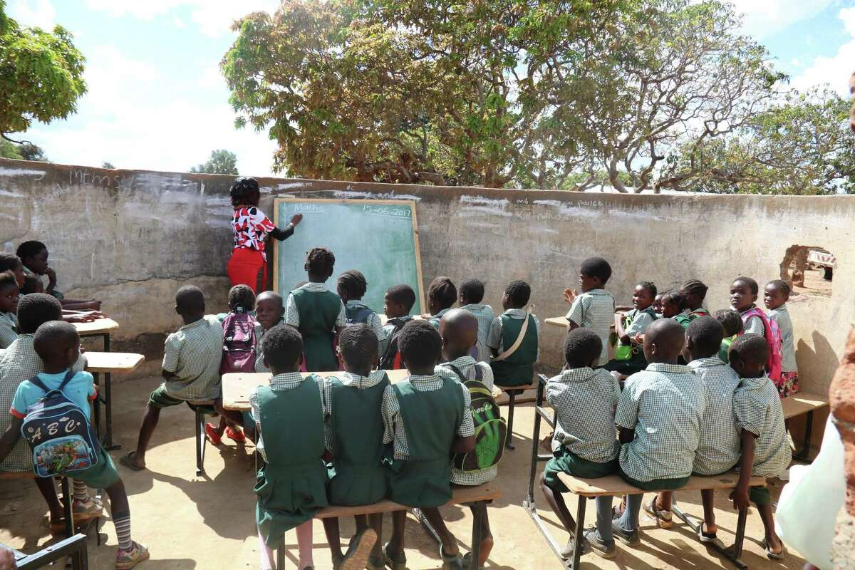A teacher writes on a chalkboard at a school in Mazabuka, Zambia. Children In Need has raised over $1 million that has helped build schools, pay teachers' salaries and renovate a local hospital.