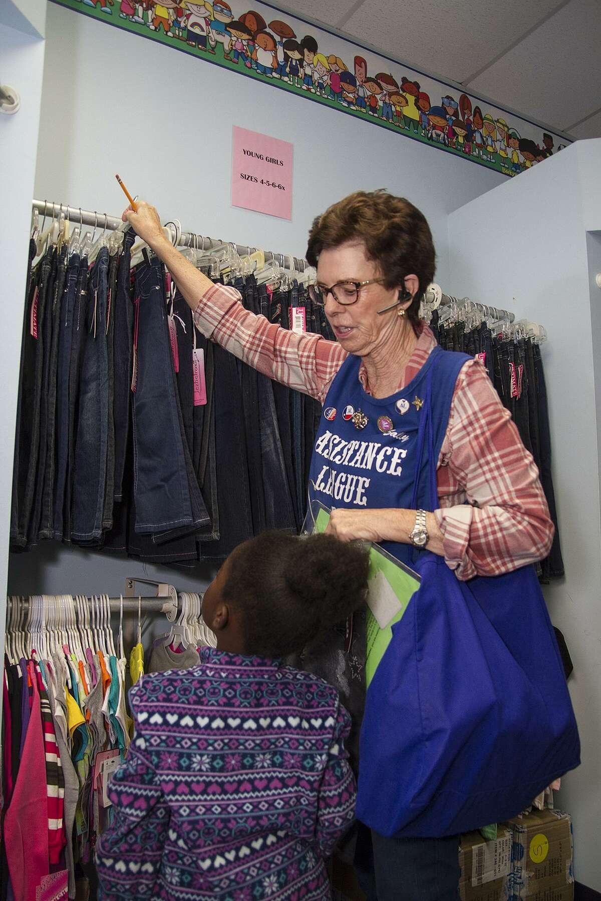 Assistance League volunteer Sally Tietz helps a child pick out clothes as part of Operation School Bell.