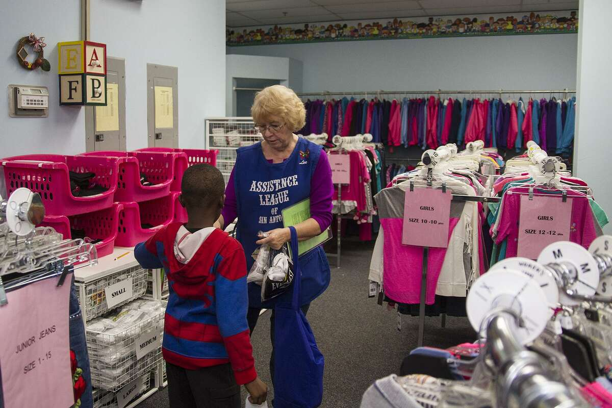 Assistance League volunteer Lee Bartels helps a child pick out clothes as part of Operation School Bell at the Assistance League of San Antonio Thrift House, Friday, Nov. 10, 2017. Operation School Bell provides kids with new clothes, a pair of shoes, school supplies, books and a jacket in the winter.
