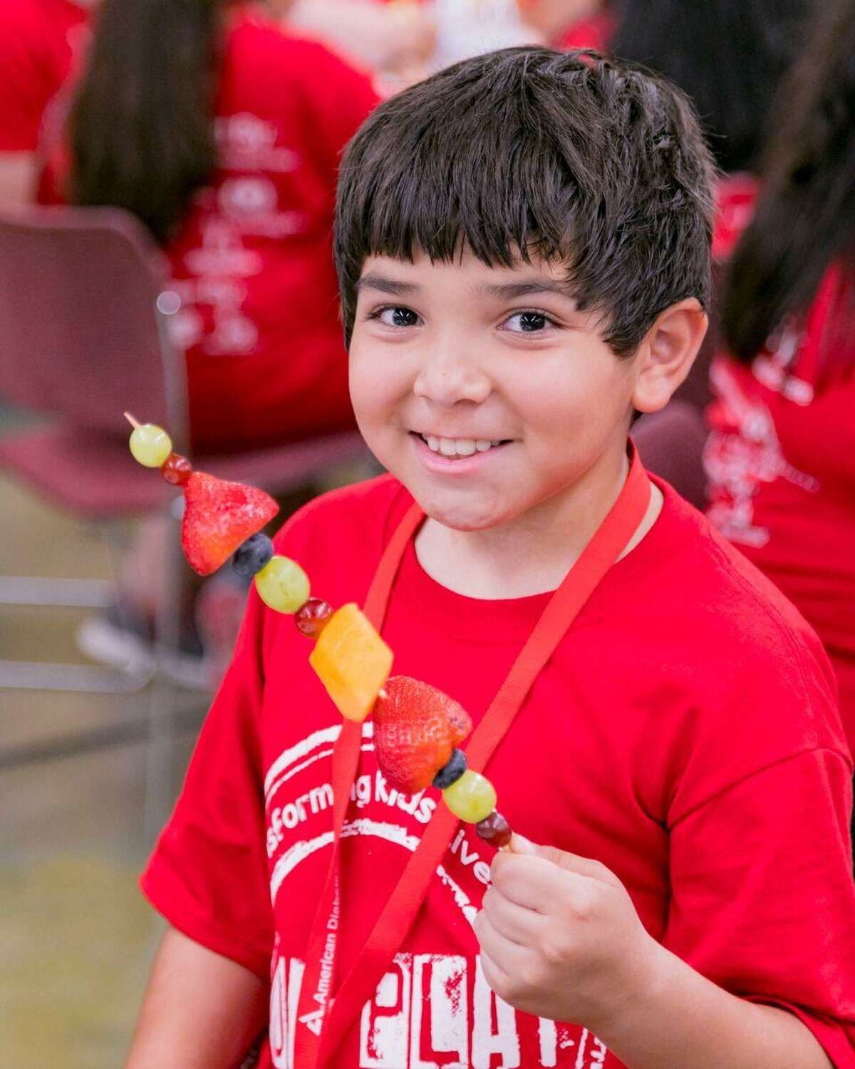 Devin Guzman enjoys a healthy snack at Camp PowerUp. The American Diabetes Association hosts the camp in San Antonio each summer for children who are at risk of developing Type 2 diabetes.