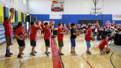 A group of children participate in basketball activities at Camp PowerUp. The American Diabetes Association hosts the camp in San Antonio each summer for children who are at risk of developing Type 2 diabetes.
