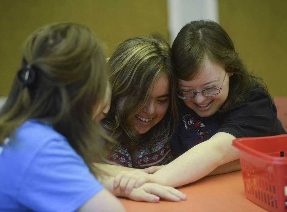Mallory Cohn (center) and  Gilver embrace as they start their day at SA Life Academy. The  organization  provides a day curriculum and field trips for adults with disabilities. Photo: Billy Calzada /