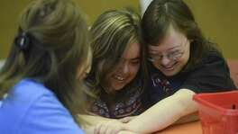 Mallory Cohn (center) and  Gilver embrace as they start their day at SA Life Academy. The  organization  provides a day curriculum and field trips for adults with disabilities.