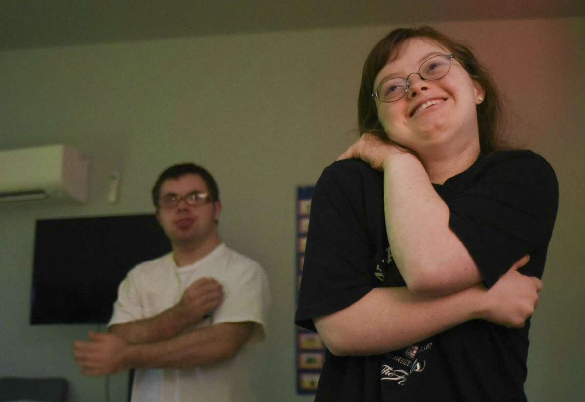 Lindsey Gilver, right, and Joey Sangco begin their day wth stretching exercises at San Antonio Life Academy, an organization that provides day curriculum and field trips for adults with disabilities. The curriculum includes social and life skills, often through field trips to various sites in San Antonio, including the Alamo Heights Fire Department, where they delivered the cookies on Friday, Nov. 3, 2017