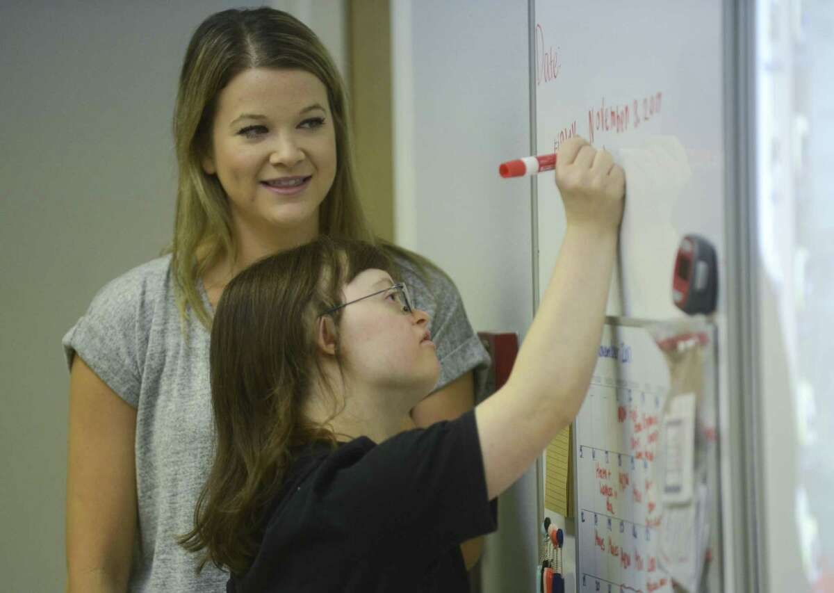 Lindsey Gilver writes the date on the board under the watchful eye of SA Life Academy instructor Samantha Pety-Grey on Nov. 3.