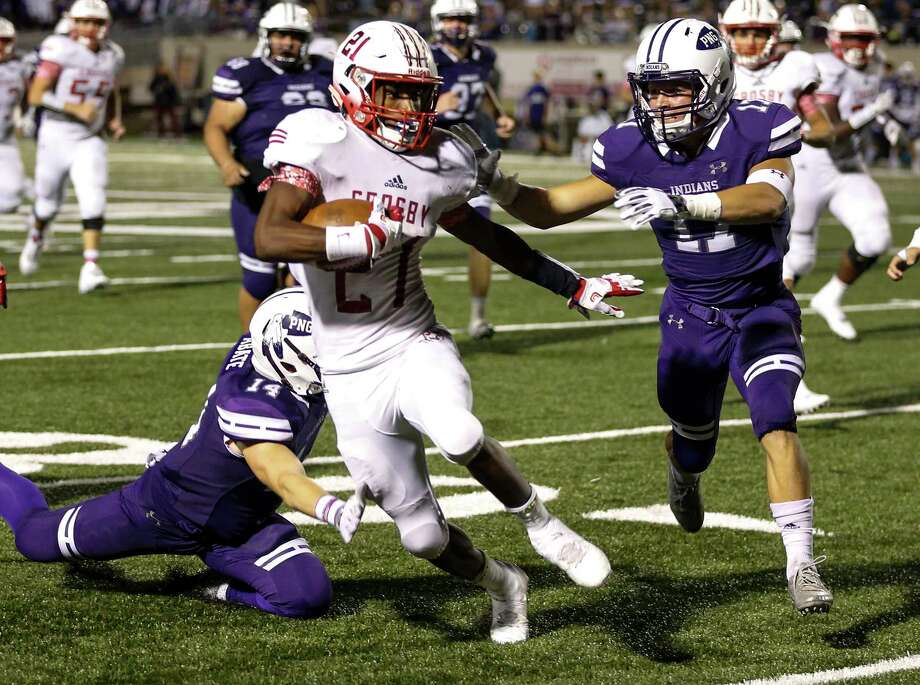 Crosby running back Craig Williams (21) runs between Port Neches-Groves defensive backs Camron Abate (14) and Zane Hernandez (17) during the third quarter of a Class 5A bi-district playoff football game at Stallworth Stadium on Friday, Nov. 17, 2017, in Baytown. Port Neches-Groves advanced in the playoffs with a 72-69 win. ( Brett Coomer / Houston Chronicle ) Photo: Brett Coomer, Staff / © 2017 Houston Chronicle