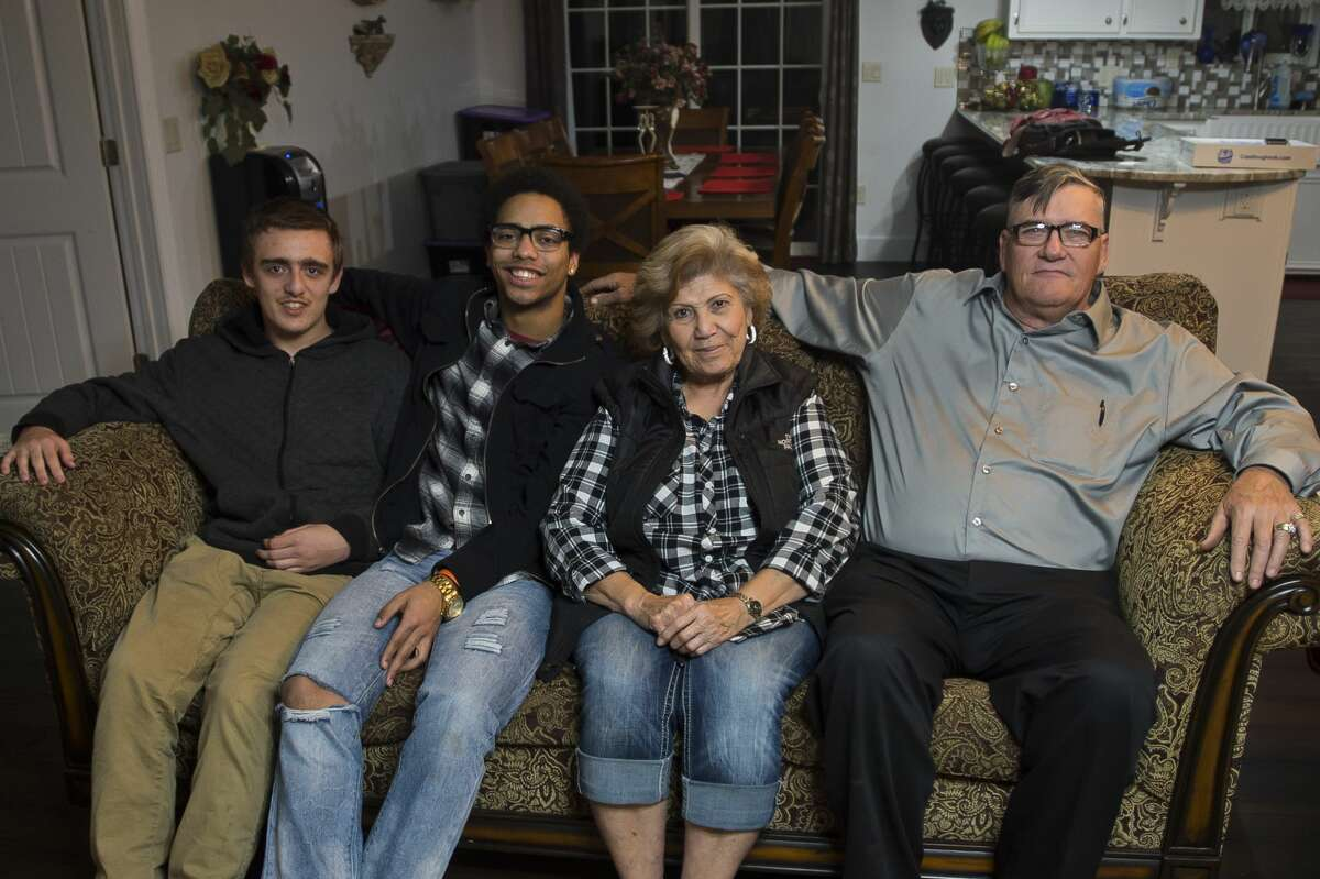 Gail Locke, right, and his wife Rachel Locke, second from right, pose for a photo with their two current foster children, David Hendrix, second from left, and Robby Novak, left, in their home in Clare County on Tuesday, Nov. 21, 2017. The Lockes have served as foster parents through the Midland County Probate Court for 25 years and have been recognized with a Congressional award for their service. (Katy Kildee/kkildee@mdn.net)