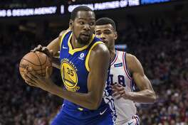 Golden State Warriors' Kevin Durant, left, in action against Philadelphia 76ers' Timothe Luwawu-Cabarrot, of France, right, during the first half of an NBA basketball game, Saturday, Nov. 18, 2017, in Philadelphia. The Warriors won 124-116. (AP Photo/Chris Szagola)