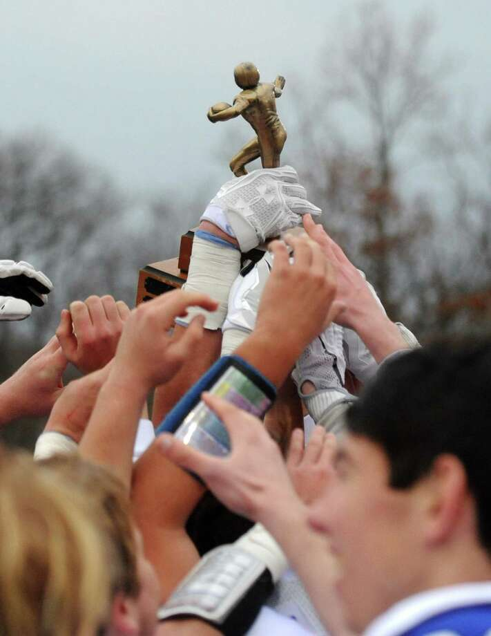 The Darien High School football team hoists their winning trophy from the Turkey Bowl high school football game at Dunning Stadium in New Canaan, Conn. Thursday, Nov. 24, 2016. Photo: Tyler Sizemore / Hearst Connecticut Media / Greenwich Time