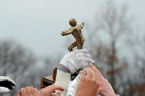 The Darien High School football team hoists their winning trophy from the Turkey Bowl high school football game at Dunning Stadium in New Canaan, Conn. Thursday, Nov. 24, 2016.