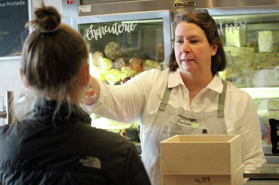 Laura Downey, co-owner of the Fairfield Cheese Shop and a certified cheese professional, helps a customer find the right cheese at the Post Road shop. Fairfield,CT. 11/21/17 Photo: Genevieve Reilly / Hearst Connecticut Media / Fairfield Citizen