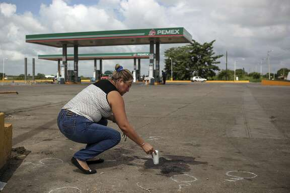 FILE - In this Aug. 23, 2017 file photo, a woman places a candle at the spot where reporter Candido Rios Vazquez was murdered the previous day at the gas station in Covarrubias, Hueyapan de Ocampo, municipality in Veracruz state, Mexico. Rios, a hard-nosed crime reporter for Diario de Acayucan, had been in Mexico�s federal protection program for journalists since 2013, its first full year, sending a chilling message to anyone else relying on the program to stay safe. (AP Photo/Felix Marquez, File)