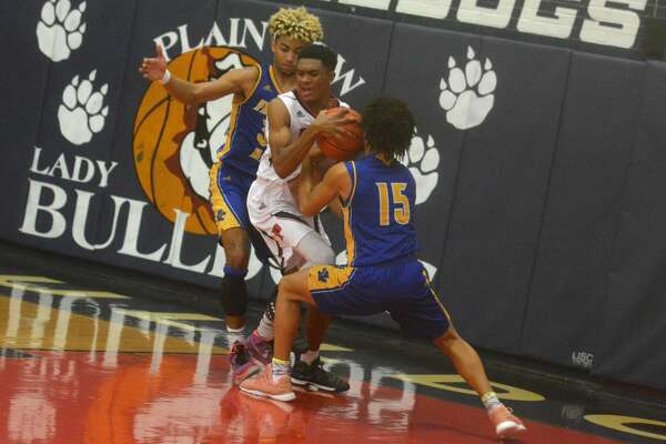 Plainview's Ryan Jackson, center, tries to maintain possession of the ball under pressure from Frenship's Skyler Newsome, left, and Jaylin Horton, 15, during a game at the Dog House Tuesday night.