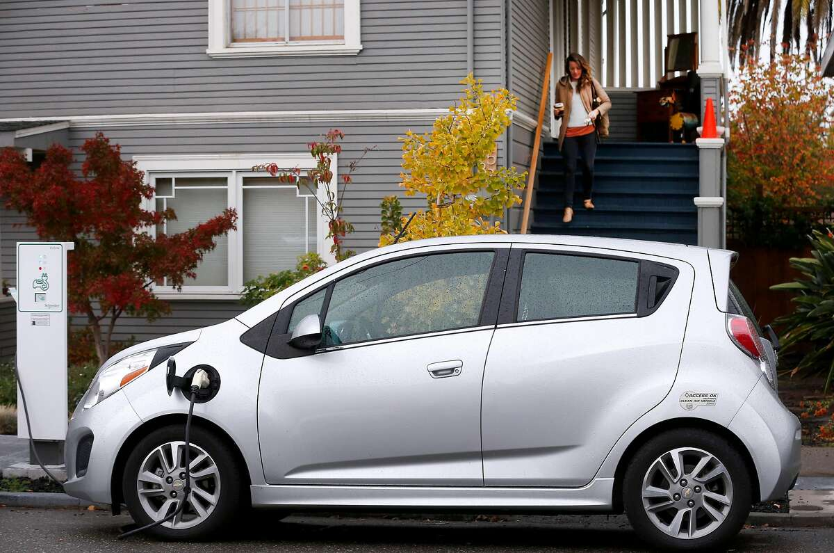 Amy Hale (upper right) leaves to unplug her electric car charging in front of her home in Berkeley, Calif. on Wednesday, Nov. 15, 2017. Amy Hale and her fianc� Bernhard Haux are participating in a pilot project by the city of Berkeley which is permitting a limited number of curbside charging stations for residents enrolled in the program.