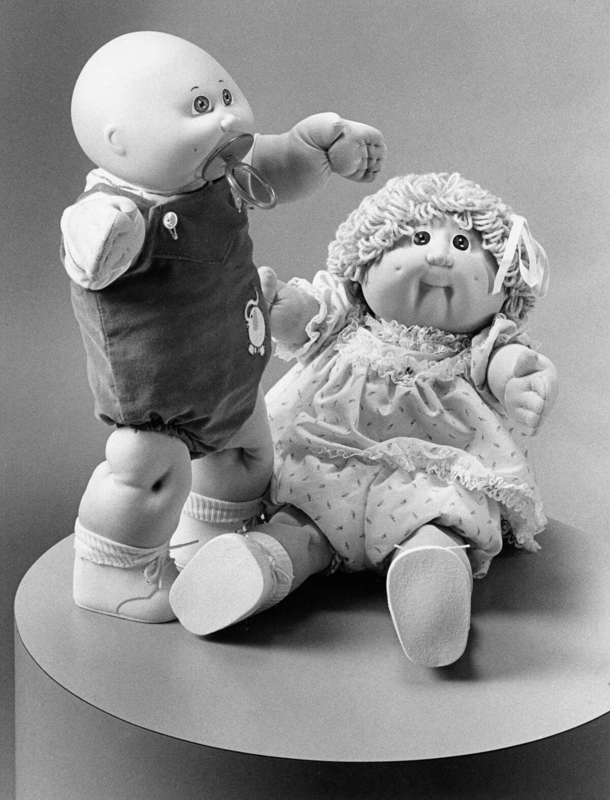 """Cabbage Patch Kids dolls, manufactured by Coleco, come with adoption papers and a birth certificate. The 16-inch dolls retail for $20 to $40 and no two are exactly alike. Demand for the dolls far exceeds supply this Christmas season. The papers on these Kids list their """"birth names"""" as Clinton Lewis and Angela Hilde."""