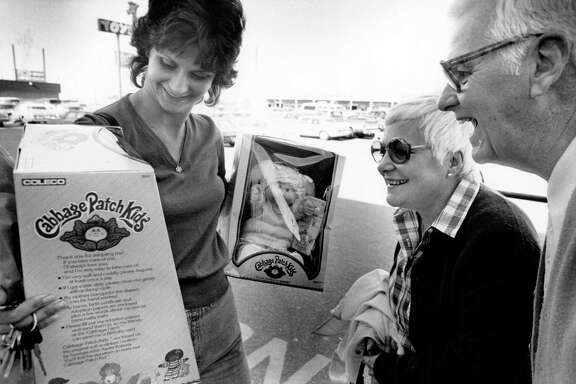 "11/25/1983 - Marilyn Zimmermann of Spring, Texas shows Mr. and Mrs. Edward Hallinan the two Cabbage Patch Kids dolls she was able to purchase at Toys ""R"" Us. The coveted dolls were selling out quickly as customers waited in long lines to buy a doll or be issued a rain check. Stores across the country were finding it difficult to keep the dolls in stock."