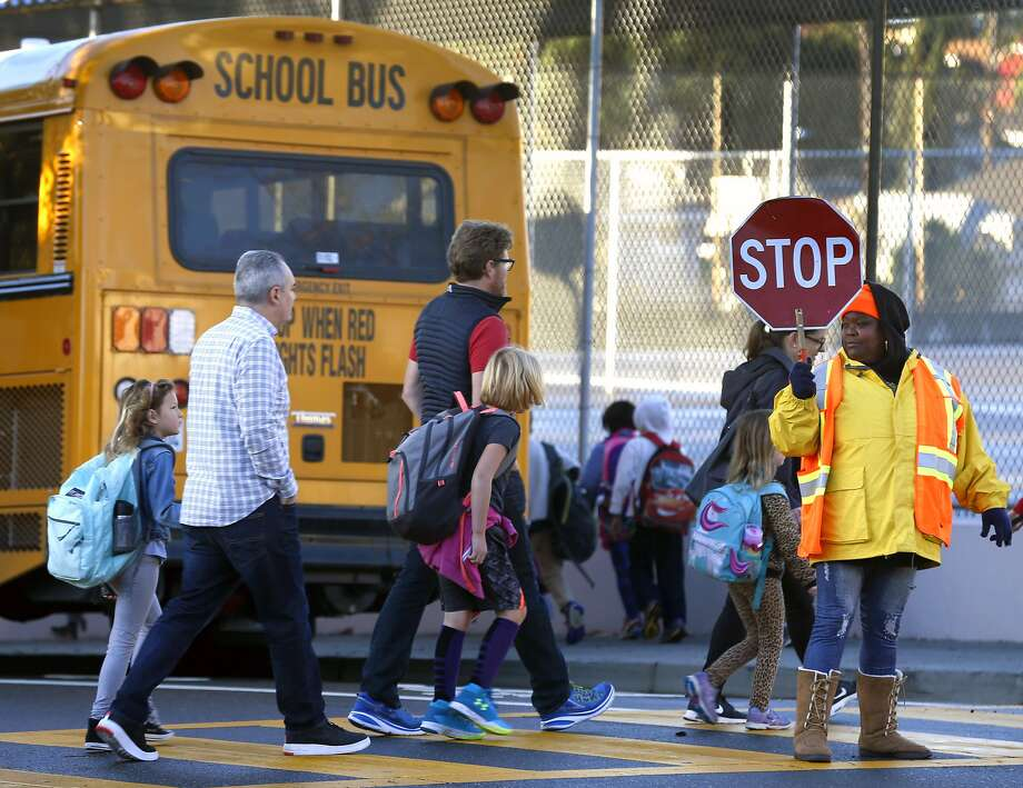 A crossing guard stops traffic for parents and Glenview Elementary School students walking to a bus staging area at East 38th and Beaumont avenues in Oakland, Calif. on Friday, Nov. 17, 2017. Students are being bused to Santa Fe Elementary in North Oakland during reconstruction of their school. Delays and increased costs in the reconstruction of Glenview Elementary have angered parents and residents. Photo: Paul Chinn, The Chronicle