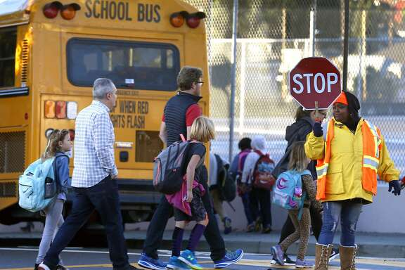 A crossing guard stops traffic for parents and Glenview Elementary School students walking to a bus staging area at East 38th and Beaumont avenues in Oakland, Calif. on Friday, Nov. 17, 2017. Students are being bused to Santa Fe Elementary in North Oakland during reconstruction of their school. Delays and increased costs in the reconstruction of Glenview Elementary have angered parents and residents.