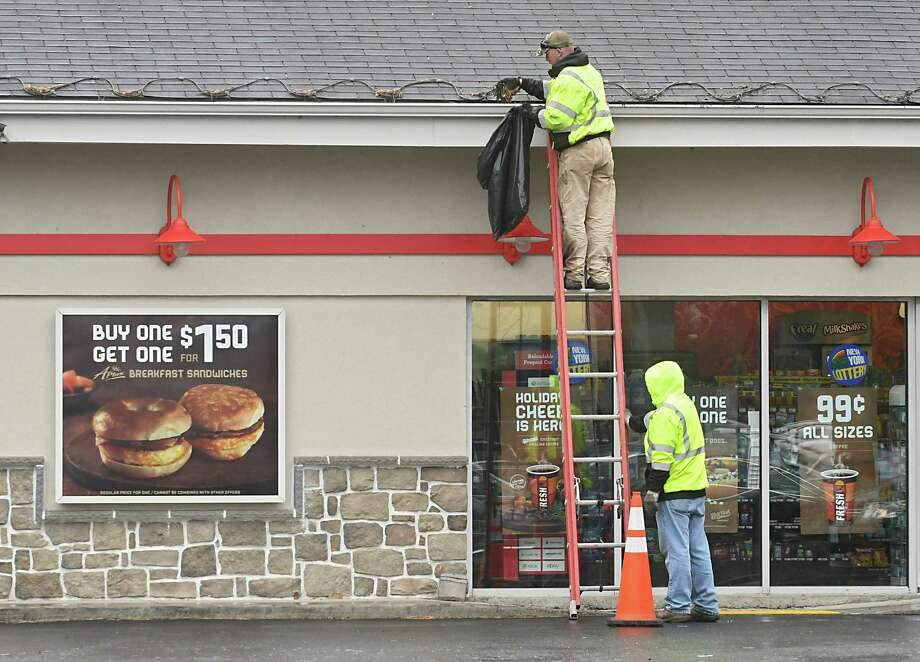 A person holds the ladder for another person cleaning out the gutter on a Sunoco station on Wednesday, Nov. 22, 2017 in Colonie, N.Y. (Lori Van Buren / Times Union) Photo: Lori Van Buren, Albany Times Union / 20042194A