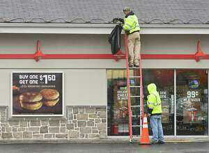 A person holds the ladder for another person cleaning out the gutter on a Sunoco station on Wednesday, Nov. 22, 2017 in Colonie, N.Y. (Lori Van Buren / Times Union)