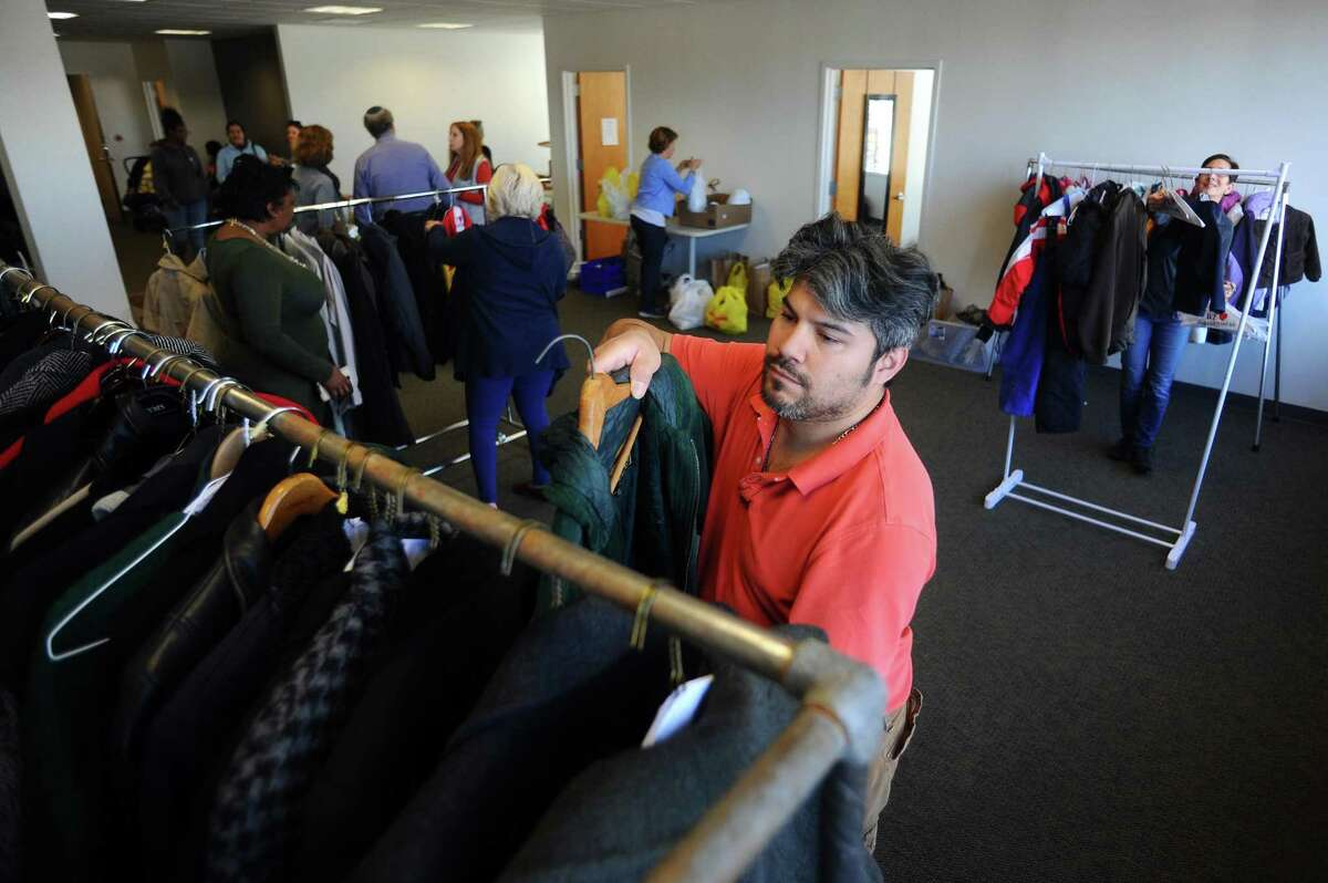 Volunteer Chris Prieto hangs coats on a hanger for clients to choose from during the Schoke Jewish Family Service of Fairfield County's coat and turkey drive on Summer Street in downtown Stamford, Conn. on Tuesday, Nov. 21, 2017.