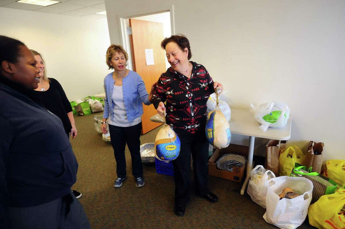 Kosher Food Pantry volunteer Jeri Appel grabs two turkeys for clients to take home during the Schoke Jewish Family Service of Fairfield County's coat and turkey drive on Summer Street in downtown Stamford, Conn. on Tuesday, Nov. 21, 2017.