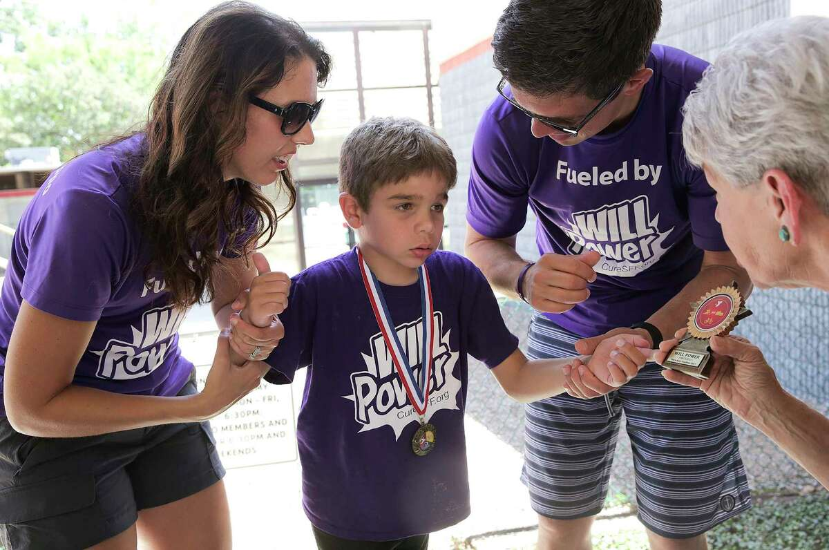 With his mom, Valerie, and dad, Tim, Will, 7, accepts an award from Roxanne Davis, community liaison for the YMCA in The Woodlands, for participating in a youth triathlon.