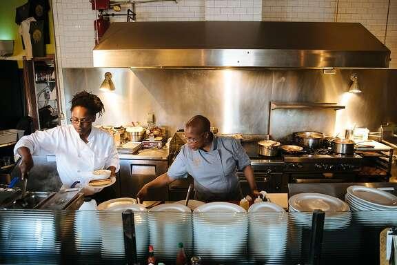 Tanya Holland helps her staff prepare food at her restaurant, Brown Sugar Kitchen, in Oakland, Calif. Friday, November 10, 2017.