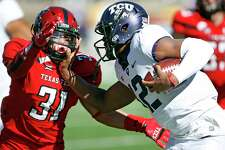 FILE - In this Saturday, Nov. 18, 2017, file photo, TCU's Shawn Robinson (12) tries to run around Texas Tech's Justus Parker (31) during the second half of an NCAA college football game in Lubbock, Texas. quarterback to step up as the regular season winds down. For the Horned Frogs, Shawn Robinson became the first true freshman quarterback to start for coach Gary Patterson in his 17 seasons as the head coach in last weekÂ?'s 27-3 win over Texas Tech. (AP Photo/Brad Tollefson, File)