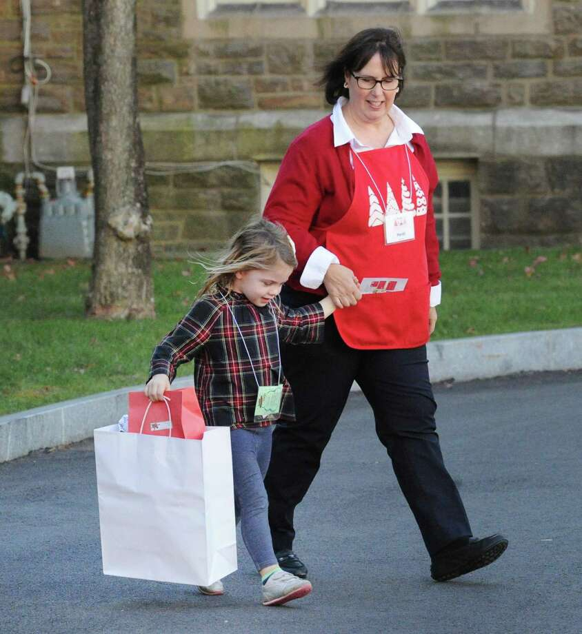 Linley Charette, 4, of Greenwich, left, holds hands with Junior League of Greenwich member Heidi Helmer after doing some Christmas shopping during the Junior League of Greenwich annual Enchanted Forest event at Christ Church in Greenwich, Conn., Friday, Nov. 17, 2017. Photo: Bob Luckey Jr. / Hearst Connecticut Media / Greenwich Time