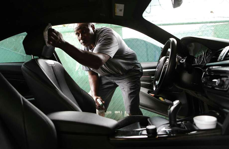 Vincent Matthews received support from the De Novo Foundation to start his business, Vincent Anointed Hand Detail, which operates out of Broadway Tire. He details a vehicleon Nov. 14, 2017. Photo: Bob Owen /San Antonio Express-News / ©2017 San Antonio Express-News