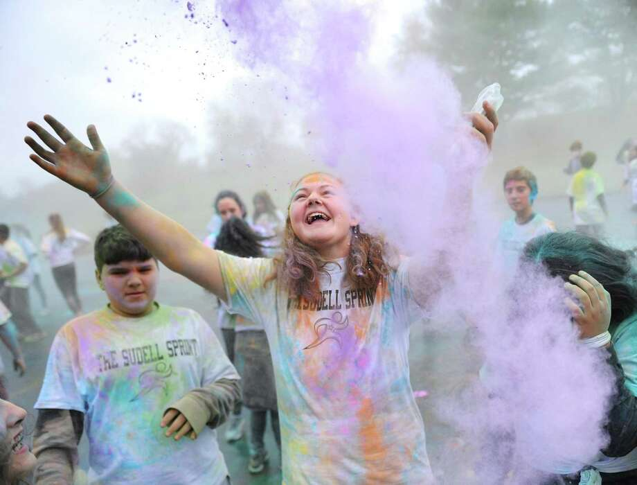 Eighth-grader Kaycee Piro celebrates as colored paint is thrown in the air during the Sudell Sprint color run at Western Middle School in Greenwich, Conn. Wednesday, Nov. 22, 2017. Eighth-graders raised $8,000 for the family of Steven Sudell, a student who is battling brain cancer, and put on a color run from the school to Hamill Rink in his honor with a pizza and ice cream party afterwards. Photo: Tyler Sizemore / Hearst Connecticut Media / Greenwich Time