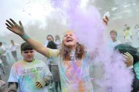 Eighth-grader Kaycee Piro celebrates as colored paint is thrown in the air during the Sudell Sprint color run at Western Middle School in Greenwich, Conn. Wednesday, Nov. 22, 2017. Eighth-graders raised $8,000 for the family of Steven Sudell, a student who is battling brain cancer, and put on a color run from the school to Hamill Rink in his honor with a pizza and ice cream party afterwards.