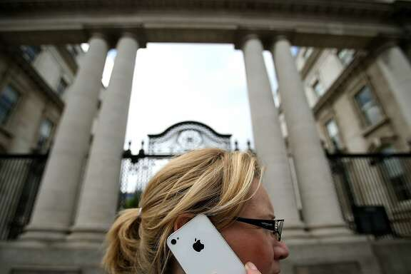 tax1124A woman on her Apple iPhone outside Government Buildings in Dublin today as Taoiseach Enda Kenny reiterated that Ireland does not negotiate specific tax deals with individual companies amid mounting criticism of Apple's corporate tax arrangements and its relationship with Ireland.   (Photo by Julien Behal/PA Images via Getty Images)