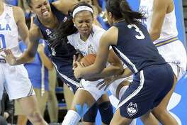 Connecticut players including guard Megan Walker (3) wrap up UCLA forward Lajahna Drummer (11) in the second half of an NCAA women's basketball game in Los Angeles Tuesday, Nov. 21, 2017. Connecticut won, 78-60. (AP Photo/Reed Saxon)
