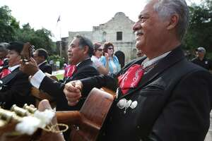 Ricardo Urbano (right), guitarist in the Mariachi Auila Azteca, plays as city leaders celebrate the announcement of the San Antonio's Spanish missions winning World Heritage Site status on July 7, 2015, in front of The Alamo.