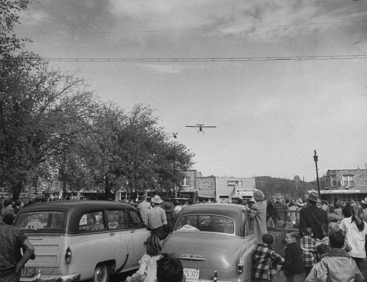 Turkey toss starts as first bird is tossed from low flying plane in Yellville, Arkansas in 1952.