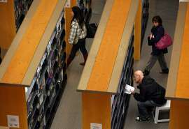 A library patron looks at a book at the main branch of the San Francisco Public Library.