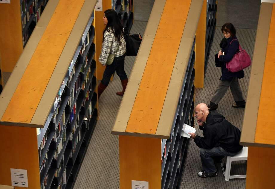 A library patron looks at a book at the main branch of the San Francisco Public Library. Photo: Justin Sullivan, Getty Images